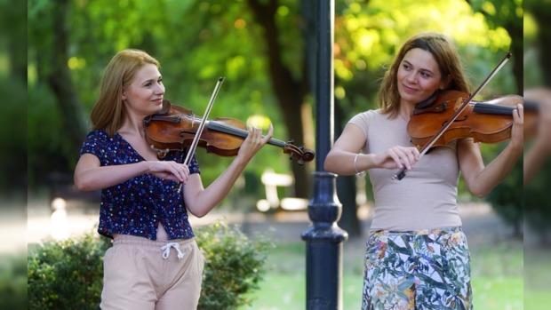 две молодые девушки играют на скрипках на свежем воздухе
