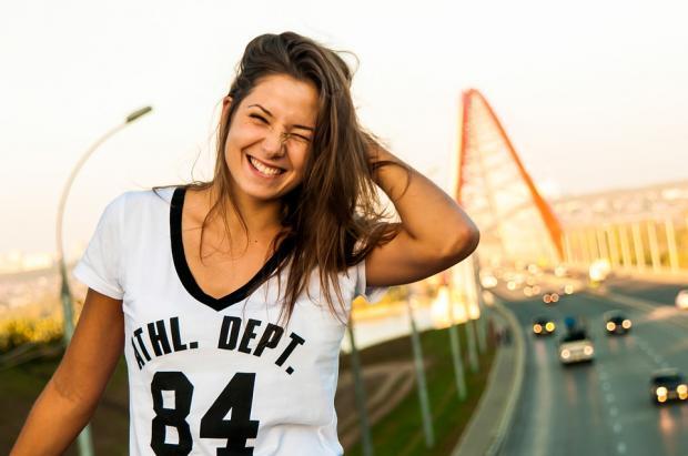 смеющаяся девушка с длинными волосами в футболке на фоне автомобильной трассы