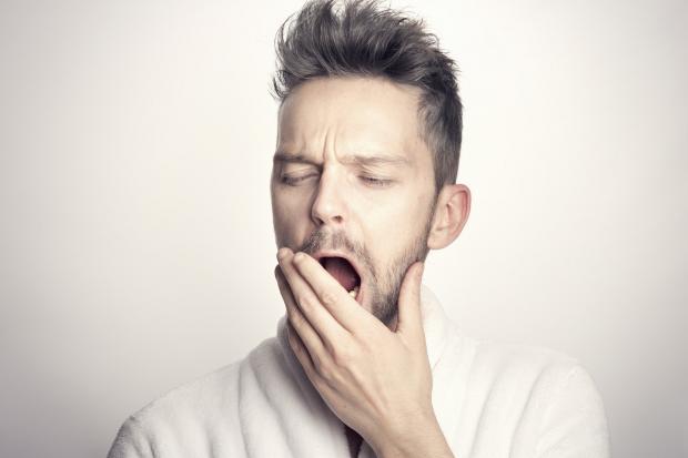 молодой человек зевает