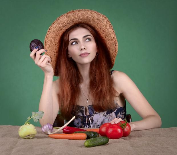 девушка в соломенной шляпке сидит за столом с овощами