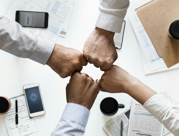 четыре руки, сжатые в кулак на столом с бумагами