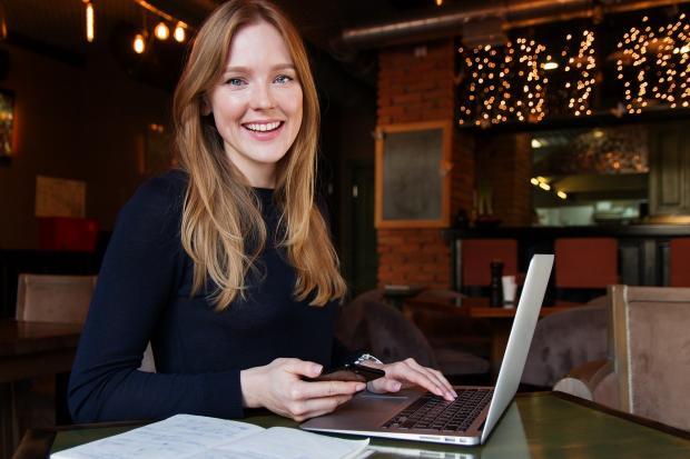 улыбающаяся девушка сидит перед открытым ноутбуком