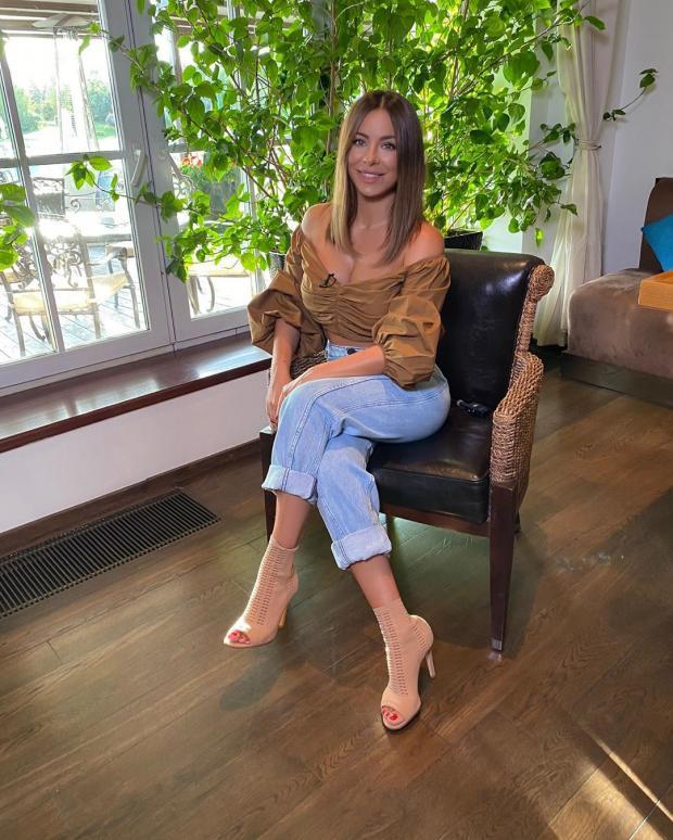 Ани Лорак в джинсах и коричневом топе сидит в кресле