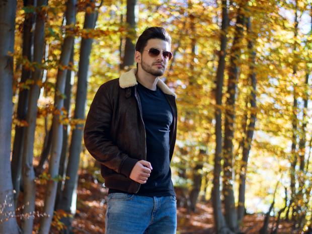 Молодой мужчина в осеннем лесу