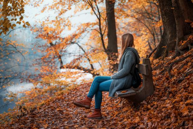 Длинноволосая девушка сидит на скамейке в осеннем парке