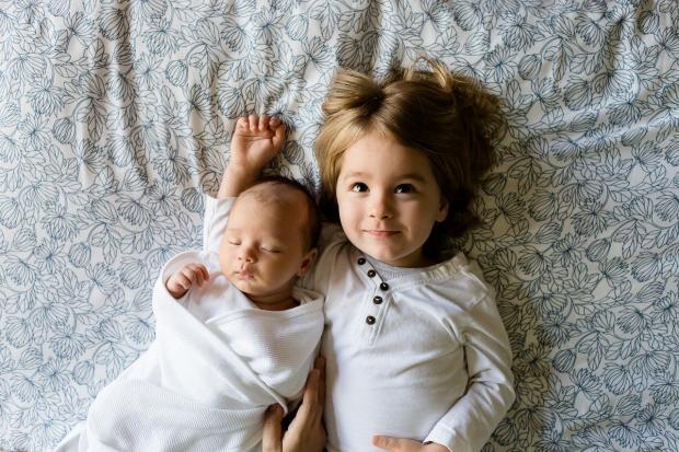 на кровати лежат двое детей в нарядах белого цвета