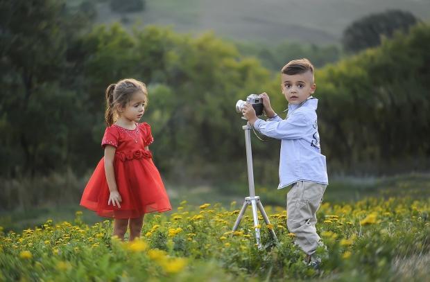 мальчик с черными глазами фотографирует маленькую девочку в красном пышном платье