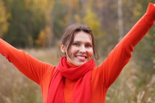 женщина в красном радостно подняла руки вверх