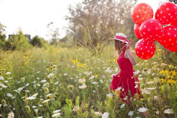 девушка со связкой красных шаров идет по полю с цветами