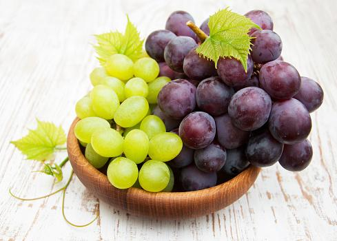 на столе стоит тарелка с виноградом