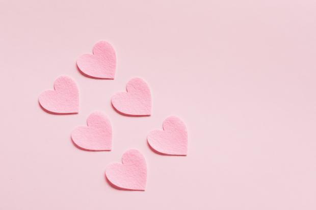 Розовые бумажные сердца на розовом фоне