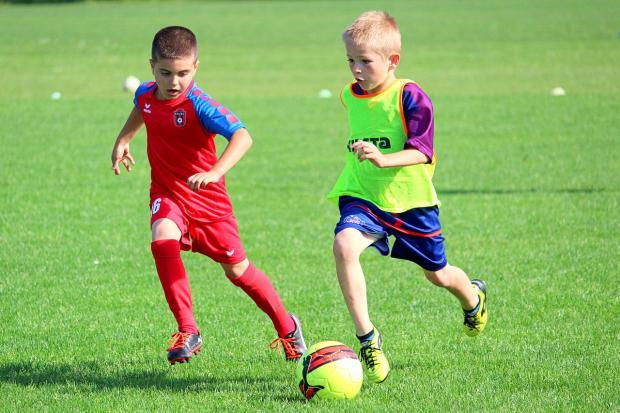 двое мальчиков бегут на футбольным мячом