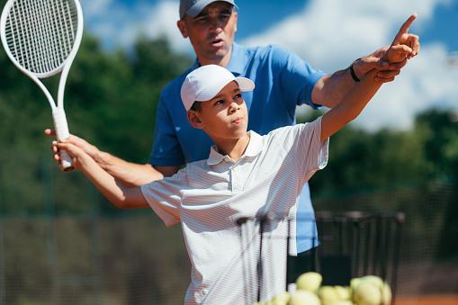 взрослый учит ребенка играть в большой теннис