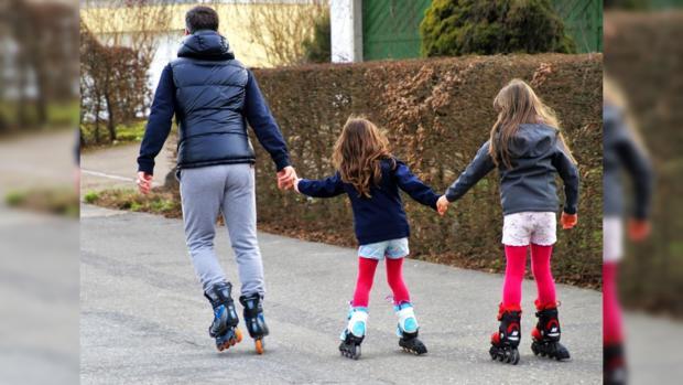 взявшиеся за руки дети едут на роликовых коньках