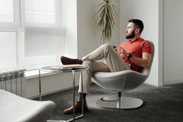Мужчина сидит в кресле и смотрит в окно