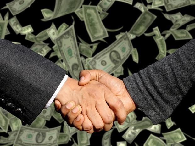 мужское рукопожатие на фоне долларовых купюр