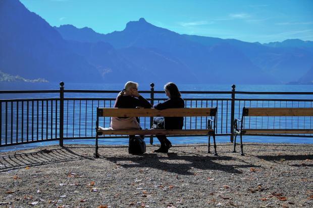 две женщина сидят на лавке и разговаривают