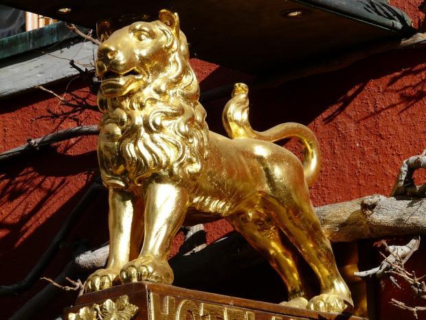 позолоченная фигура льва как украшение колонны