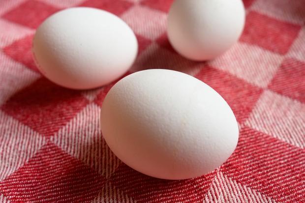 белые вареные яйца лежат на скатерти в красную клетку