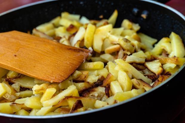 стоит сковорода с жареным картофелем и деревянной лопаткой
