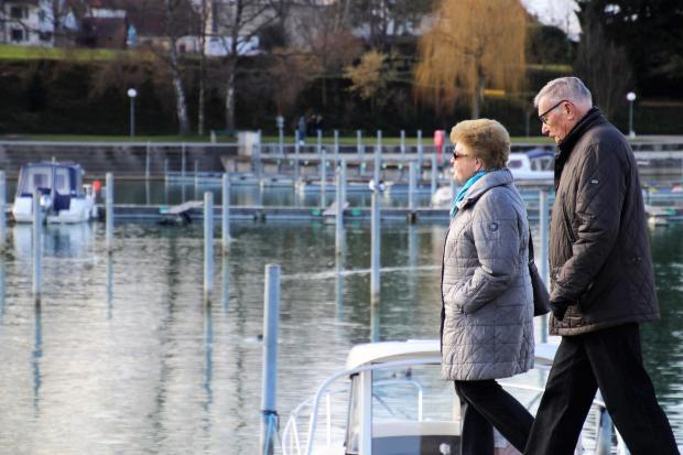 пожилые люди прогуливаются у реки