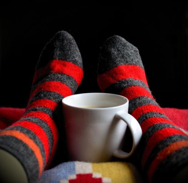 ноги в полосатых носках обнимают чашку