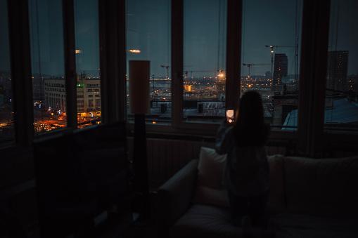 девушка ночью смотрит в окно