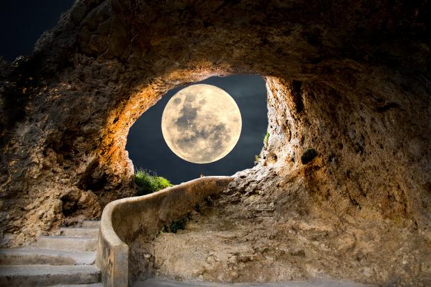 полная луна видна на небе сквозь горы