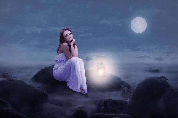 одинокая девушка в белом платье сидит на камнях в Полнолуние