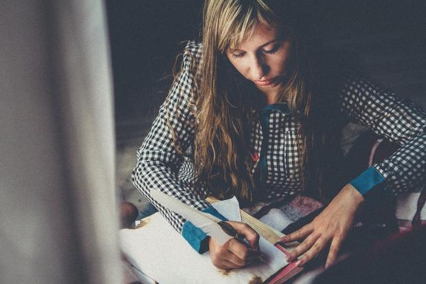 девушка с распущенными волосами пишет на бумаге гусиным пером