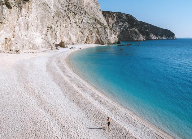 Человек бежит по песчаному пляжу
