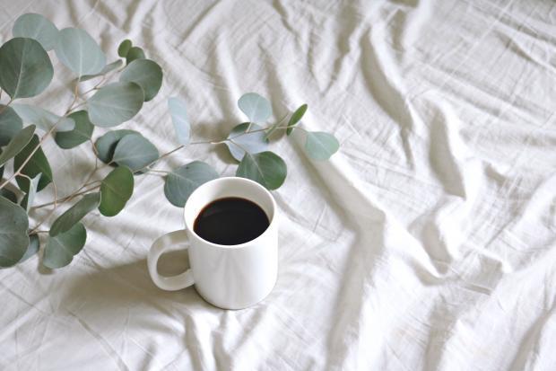 Чашка кофе на белой постели