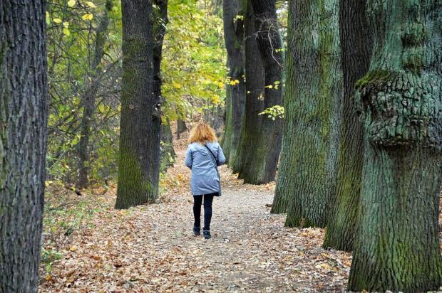 девушка в голубой куртке идет по осенней аллее