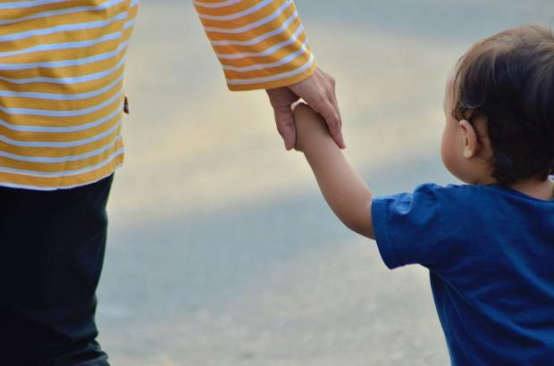 малыш в синей футболке идет за руку с мамой в полосатом джемпере
