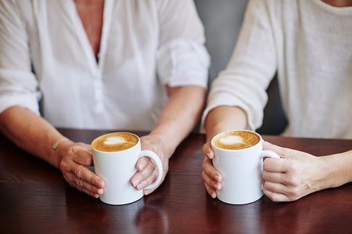 двое собеседников держат в руках кружки с кофе