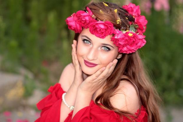 улыбается красивая девушка в красном платье и венке из красных цветов