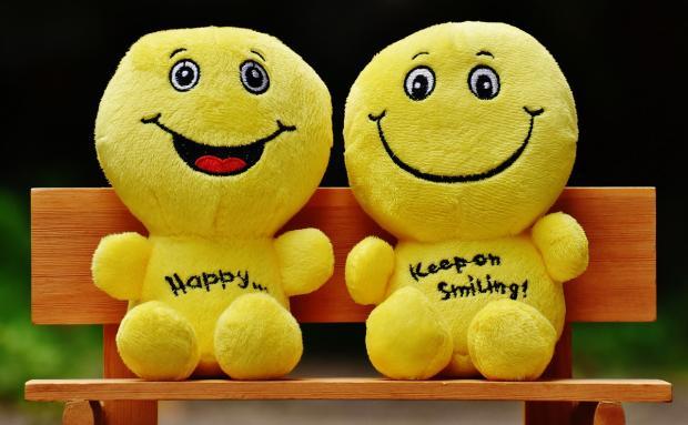 мягкие игрушки в виде улыбающихся смайликов сидят на деревянной скамейке