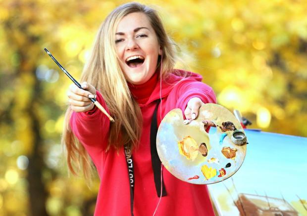 блондинка в красном протягивает мольберт с красками и кисть для рисования