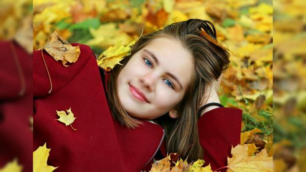девушка в бордовом пальто лежит на охапке осенних листьев