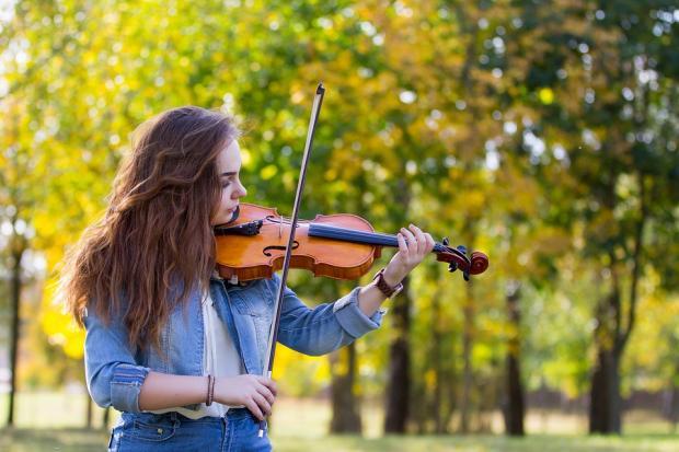 девушка с распущенными волосами в синем играет на скрипке на природе
