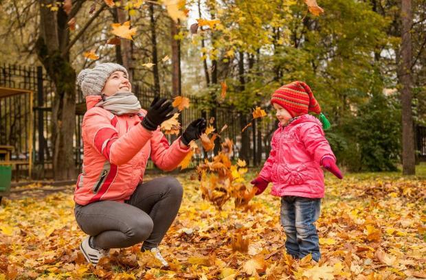 мама с ребенком играют листьями