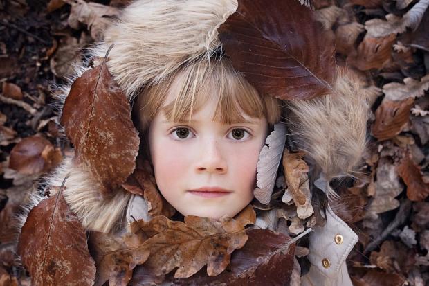 девочка с осенними листьями на капюшоне