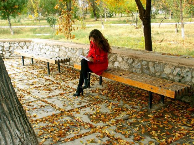 девушка в красном пальто на скамейке читает книгу