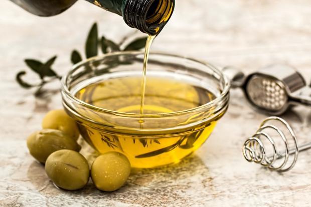 из бутылки наливают оливковое масло в стеклянную плошку