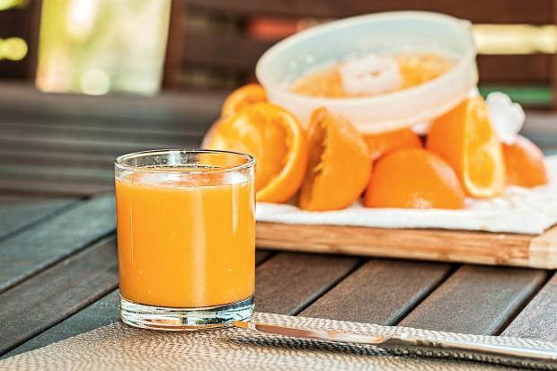 стакан свежевыжатого апельсинового сока и половинки апельсинов на заднем плане