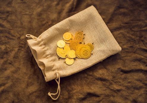 золотые монеты лежат на полотняном мешочке