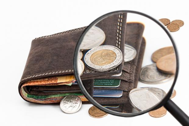 кошелек с банковскими картами и монетами под лупой