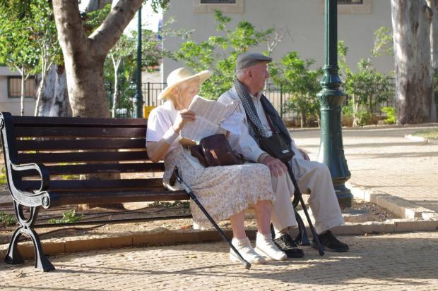 пожилая пара сидит на скамейке, женщина читает газету