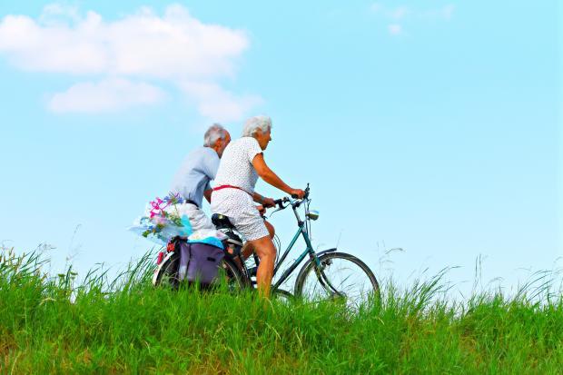 пожилая пара едет на велосипедах
