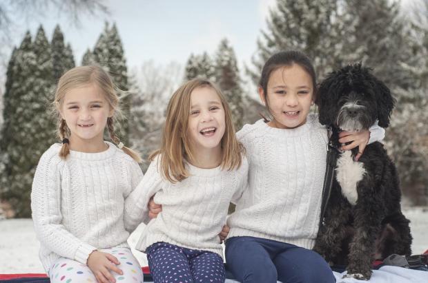 трое детей в белых джемперах сидят на скамейке в обнимку с большой черной собакой